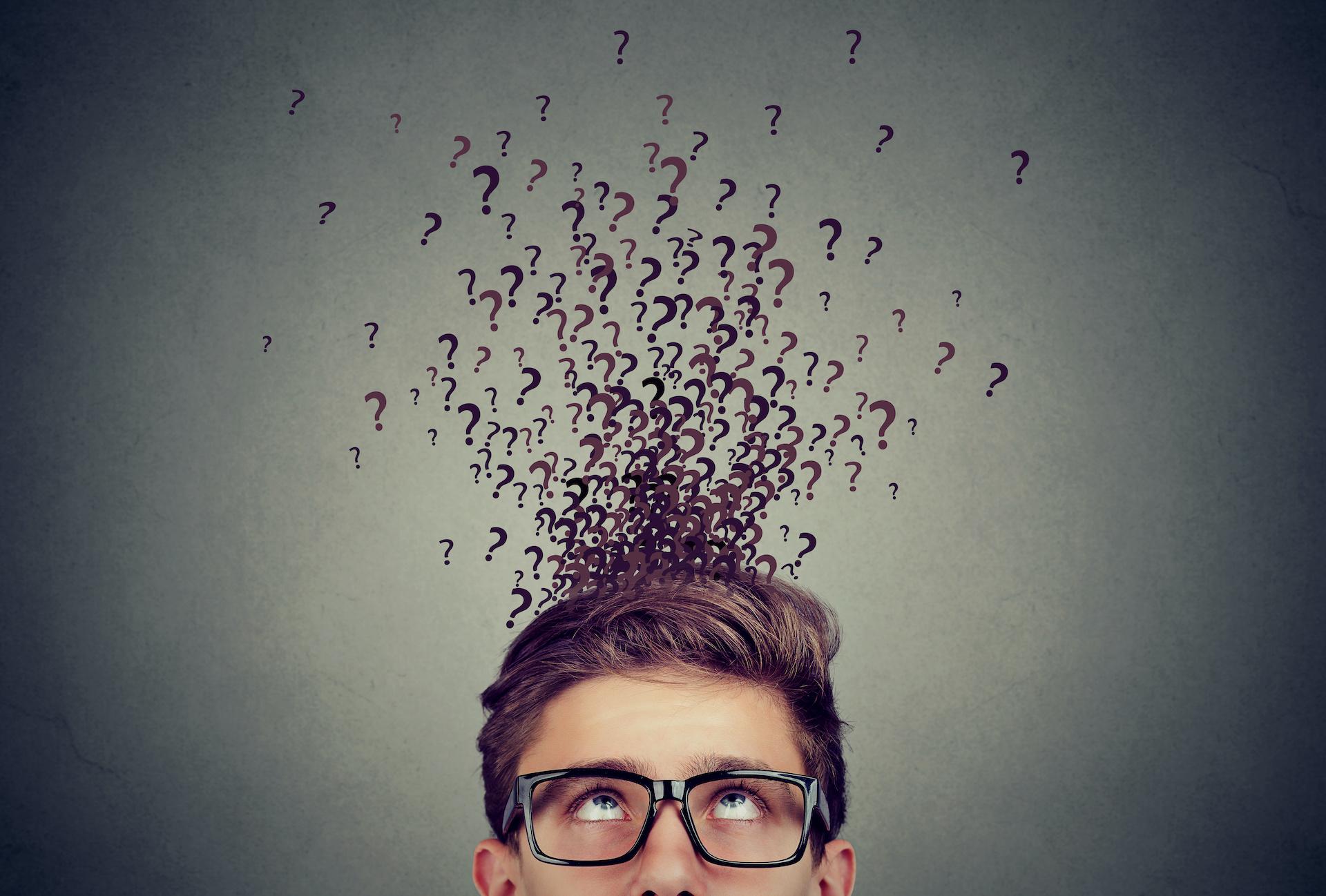 Oczy mężczyzny skierowane na wychodzącą z jego głowy chmurę ze znakami zapytania.